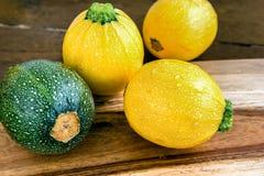 Сырцовый круглый желтый и зеленый цукини на деревянной предпосылке Стоковое фото RF