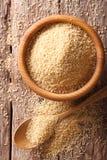Сырцовый кускус в деревянном конце-вверх шара и ложки по вертикали верхняя часть v Стоковые Изображения RF