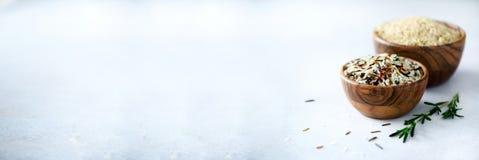Сырцовый органический коричневый рис в деревянных шаре и розмариновом масле на светлой конкретной предпосылке пицца ингридиентов  Стоковая Фотография RF