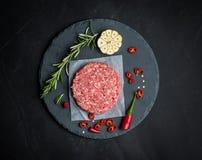 Сырцовый пирожок говядины бургера на каменной предпосылке Стоковые Изображения