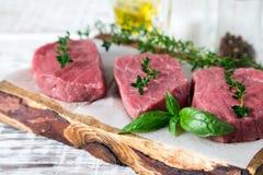 Сырцовый стейк говядины на светлой деревянной предпосылке с оливковым маслом и s Стоковые Изображения