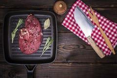 Сырцовый стейк говядины с специями на черной сковороде Стоковое Изображение