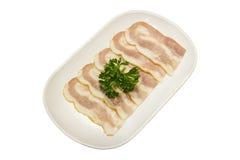 Сырцовый сух-вылеченный бекон на изолированном блюде, стоковая фотография