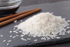 Сырцовый basmati рис разбросан на черный шифер установьте текст стоковая фотография