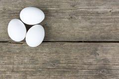 3 сырцовых белых яичка курицы на старом винтажном деревянном столе Стоковые Фото