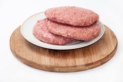 3 сырцовых бургера на плите готовой для жарить Стоковое фото RF