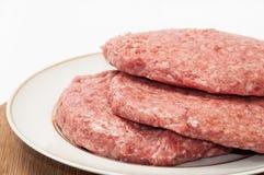 3 сырцовых бургера на плите готовой для жарить Стоковое Фото