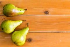 3 сырцовых зеленых груши на деревянном столе таблицы Стоковая Фотография RF