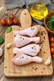 4 сырцовых drumsticks цыпленка на светлой разделочной доске с томатами, шпинатом, специями и шпинатом Стоковое Изображение
