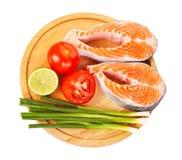 2 сырцовых salmon стейка с томатами, известкой и зеленым луком Стоковые Изображения