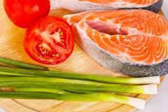 2 сырцовых salmon стейка с томатами, известкой и зеленым луком на th Стоковые Фото