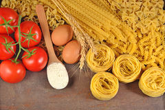 Сырые итальянские макаронные изделия, зрелые томаты разветвляют, мука и яичка Стоковые Фотографии RF