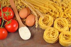 Сырые итальянские макаронные изделия, зрелые томаты разветвляют, мука и яичка Стоковая Фотография RF