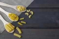 Сырые макаронные изделия в деревянной ложке стоковое фото rf
