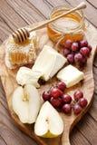 Сыр, виноградина и мед на деревянной доске Стоковые Изображения
