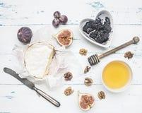Сыр камамбера на белой упаковочной бумаге, с вареньем, грецкими орехами и медом, свежими смоквами, на деревенской деревянной пред стоковое фото rf