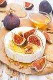 Сыр камамбера с медом, смоквами, грецкими орехами и шутихами на борту Стоковая Фотография