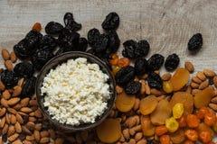 Сыр коттеджа в белой тарелке Черносливы, высушенные абрикосы, высушенные мандарины и миндалины на светлой деревянной предпосылке Стоковые Фотографии RF