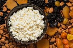 Сыр коттеджа в белой тарелке Черносливы, высушенные абрикосы, высушенные мандарины и конец-вверх миндалин Стоковое фото RF