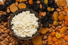 Сыр коттеджа в белой тарелке Черносливы, высушенные абрикосы, высушенные мандарины и конец-вверх миндалин Стоковая Фотография RF