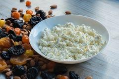 Сыр коттеджа в белой тарелке Черносливы, высушенные абрикосы, высушенные мандарины и миндалины на светлой деревянной предпосылке Стоковое фото RF