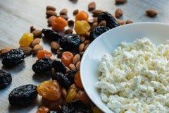 Сыр коттеджа в белой тарелке Черносливы, высушенные абрикосы, высушенные мандарины и миндалины на светлой деревянной предпосылке Стоковое Изображение RF