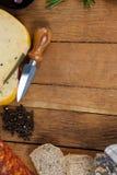 Сыр, нож, черный перец и хлеб на прерывая доске Стоковая Фотография