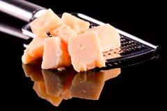 Сыр пармесан и терка на черной лоснистой таблице с отражением Сыр пармесан изолированный на черной предпосылке Стоковое Изображение RF