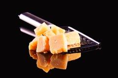 Сыр пармесан и терка на черной лоснистой таблице с отражением Сыр пармесан изолированный на черной предпосылке Стоковые Изображения RF