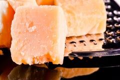 Сыр пармесан и терка на черной лоснистой таблице с отражением Сыр пармесан изолированный на черной предпосылке Стоковое фото RF
