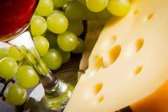 Сыр, стекло красного вина в стекле и пригорошня виноградин Стоковое Фото