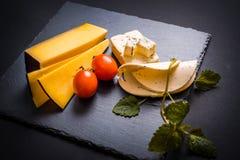 Сыр с прессформой, томатами вишни, базиликом и Мелиссой зеленеет, накаленный докрасна перец на каменном подносе на темноте - сера Стоковое Фото