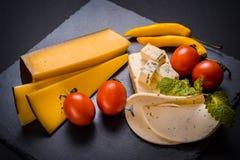 Сыр с прессформой, томатами вишни, базиликом и Мелиссой зеленеет, накаленный докрасна перец на каменном подносе на темноте - сера Стоковое Изображение