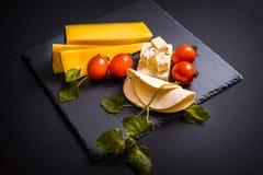 Сыр с прессформой, томатами вишни, базиликом и Мелиссой зеленеет, накаленный докрасна перец на каменном подносе на темноте - сера Стоковое Изображение RF
