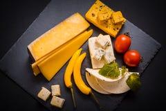 Сыр с прессформой, томатами вишни, базиликом и Мелиссой зеленеет, накаленный докрасна перец на каменном подносе на темноте - сера Стоковые Фото