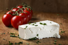 Сыр фета с пуком томатов вишни в предпосылке на древесине Стоковые Фото