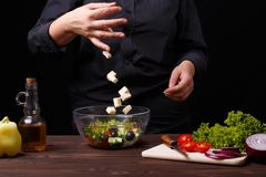 Сыр шеф-повара падая к шару с греческим салатом, варочным процессом стоковые фото