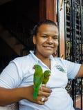 Сь молодая женщина держа 2 зеленых попыгая на ее руке Стоковые Изображения