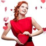 Сь red-haired девушка держа красное сердце стоковое изображение