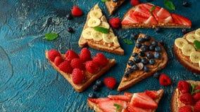 Сэндвичи арахисового масла со свежими тостами еды клубники, голубики, поленики и банана всеми стоковое фото