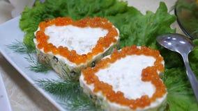 Сэндвичи с красной икрой в форме сердца и с укропом на плите и листах салата Праздничная обедая таблица сток-видео