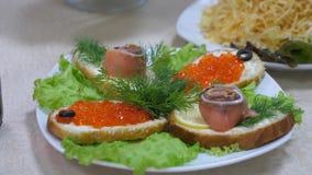 Сэндвичи с красными рыбами и красными икрой и укропом на плите и листах салата Праздничная обедая таблица очень вкусная еда дальш видеоматериал