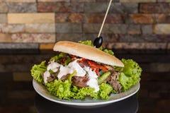 Сэндвич мяса с салатом, луком, грибами, перцем и майонезом с предпосылкой кирпичной стены стоковая фотография rf