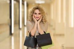 Сюрприз женщины держит щеки вручную Красивая девушка при хозяйственные сумки смотря камеру Стоковое фото RF