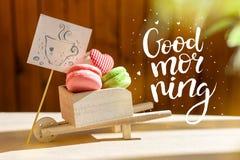Сюрприз утра, покрашенные makarons тортов с карточкой Надпись доброе утро Лучи Солнця стоковые фотографии rf