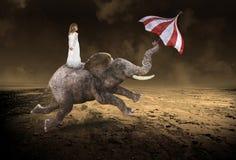 Сюрреалистическая маленькая девочка, слон летая, запустелая пустыня стоковые фото