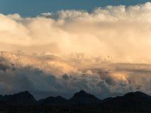 Сюрреалистические облака вдоль черных гор стоковое фото