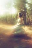 Сюрреалистическая запачканная предпосылка молодой женщины сидя на камне в лесе стоковые фотографии rf