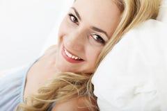 Ся счастливая женщина ослабляя в кровати стоковая фотография rf