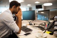 Слабонервный руководитель бизнеса сидя в офисе стоковое фото rf